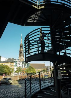 Sihoulettes Of Hamburg by Marina Usmanskaya  Silhouette of the spiral staircase of the bridge in the Hafencity in Hamburg Germany with a view of the church through the canal  #MarinaUsmanskayaFineArtPhotography #ArtForHome  #HomeDecor #FineArtPrints #Hamburg #ArtPrints #travel