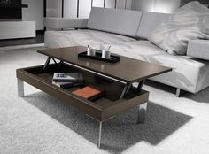 Entre el sofá y el mueble para la televisión, si se dispone de espacio suficiente, es ideal colocar una mesa de centro. La mesa de centro, a parte de ayudar a definir la zona, sirve para dejar libros, revistas… o incluso para poner los pies.
