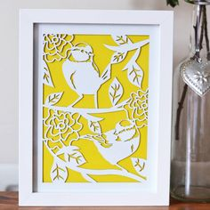 This is a handmade (designed by myself) framed laser cut printThe design features two blue tit's (a firm British favourite!) in among flora and fauna. The print, measuring 18 x 24cm framed, would make a lovely gift for yourself or someone special at any time of year. Personal commissions are also available so please get in touch for more information via the 'ask seller a question' button. :) Please note that all items are made to order.Design is cut on 1.3mm mountboard. Frame - White coated…
