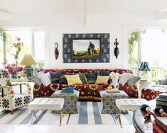 Sig Bergamin's beach house in Bahia Brazil:  In the living room, the sofa and ottomans were designed by Bergamin, the armchair (left) is African, and the Barcelona stools are by Mies van der Rohe; Kenyan masks flank a 19th-century painting found at a flea market.