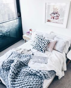 Minimalist white and grey room with a cozy merino throw and furry pillows.
