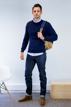 business casual outfits, dark navy sweater over light blue shirt, dark blue jeans and brown leather shoes, worn by man with camel brown backpack