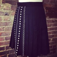 Playing with pleats. Metallic lace, nail heads, & zipper add texture and shine to black wool. Ellipse original. Size 2, $125