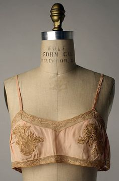 French Brassiere and Underpants, Met Museum, 1920s..The Flat Chest of the Twenties... The slender flat-chested tanned body and face of a 15 year old became the desired silhouette of the bright young things of the 1920s. None of the bras gave much shape, but few ladies were seeking anything more than stopping the bust from wobbling. As long as they looked boyish they looked fashionable.