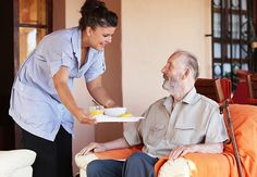 caregiver giving senior man a meal, to illustrate home care