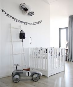 white nursery room in Scandinavian style contains white crib and white ladder