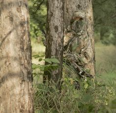A hunter wearing Realtree APG ™ camo stands in a green grassy area in a small stand of trees,
