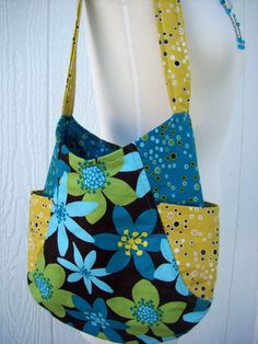 Very trendy 241 tote bag. Beautiful cotton floral center panel with two coordinating cotton prints make this a lovely tote bag, purse, or small diaper bag. The bag as 2 outside pockets and 1 inside pocket. The bag stays securely closed with a magnetic snap. I have padded the handle for added comfort. Dimensions: 13 wide, 12 tall, and a 5 wide base. The handle is 1 1/2 wide and 25 long. Cotton canvas between the layers of fabric give this bag a very nice feel. Pattern designed by : Ann...