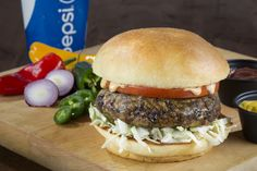 GOYA Veggie Burger – A yellow rice patty with black beans, platanos maduros, peppers and onions served with sliced tomato, shredded green cabbage and chipotle aioli on a toasted bun. - GOYA Latin Grill, Section 105