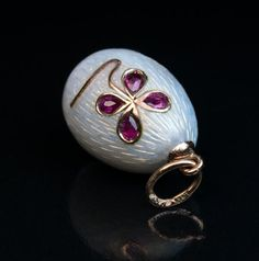 This is a rare original tsarist era Faberge miniature egg pendant, 1908-1917. The egg is covered with a pearl white guilloche enamel and embellished with a four petal flower designed in Art Nouveau taste. The flower is set with four pear cut rubies.