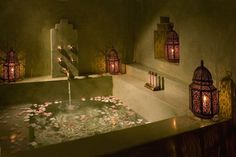 A deep bathtub with rose petals and Moroccan lanterns... Inside the lanterns are votive candles. We wonder if they're scented.