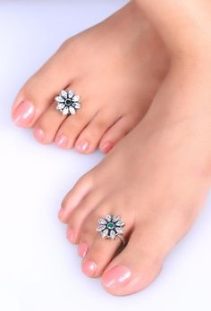 Even on the simplest of footwear, these flower shaped zircon studded toe rings will make your feet stand out.Comes with an adjustable wire enclosure with rounded & filed ends to ensure comfortable pinch free fit. Dimension: Diameter Weight: 11.02 gm Color: Green & silver Closure: Adjustable Material: 92.5% sterling silver Finish: Hand crafted Inspiration: Banjara tribe, Rajasthan
