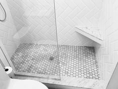 Marble and white subway bathroom shower. White beveled subway tile laid in herringbone pattern. Floor: marble hexagon mosaic sheet tile.