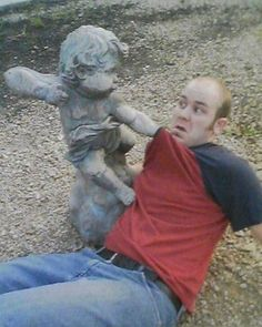 24 Hilarious Pics Of People Posing With Statues: That's One Tough Cupid.