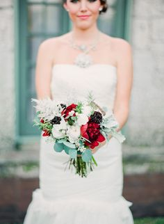 A stunning red, white, and green wedding bouquet. The pinecone addition adds a hint of Christmas without being overboard.