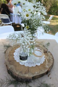 Centerpiece - white tablecloth, burlap square, fern fronds, tree slice, doily, vases with daisies, baby's breath, and candles. We used double sided tape to keep the burlap and doilies from blowing in the wind.