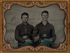 Two unidentified soldiers in Union uniforms in front of painted backdrop showing military camp scene. Photographed between 1861 and 1865 as a hand colored quarter plate tintype. at 12.5 x 10 cm.åÊ Pho