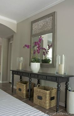 Pottery Barn Console with large hurricane candle holders, a huge gray mirror and baskets underneath. Love this look!