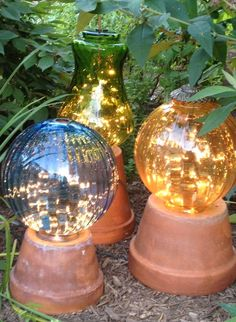 DIY - Garden lights made from flower pots and old lamp globes with strings of white lights in the globes.