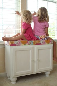 Turn a Set of Cabinets into a Storage Bench by adding some furniture legs and a seat cushion.