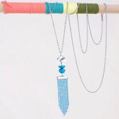 Telle une sculpture verticale ce collier joue sur la superposition de plusieurs éléments.Il est composé de perles de turquoise naturelle et d'une chaine billes