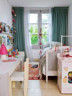 Dormitorio de una nena con piso calcáreo crudo y cortinas de pana verde con viso blanco; cama patinada con esterilla y estantes de chapa pintados de blanco.