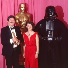 "John Mollo, holding his Oscar for Costume Design for his work on ""Star Wars"", presenter Natalie Wood and an unidentified Sith Lord backstage at the Oscars in 1978. ""Star Wars"" took home a total of seven statuettes that night."