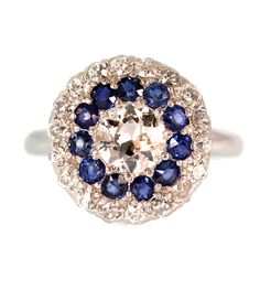 This 1940's beauty features a 0.85 carat Old European cut diamond in the center surrounded by eleven (11) mixed cut blue Sapphires and another halo of eighteen (18) Old European cut diamonds all set i
