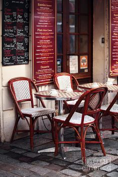 A very typical Paris Cafe with French Bistro Furniture: small round tables, woven rattan seated chairs, and the menu and carte du jour on the wall outside.