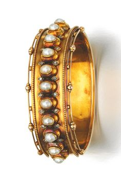GOLD, HALF-PEARL AND DIAMOND BANGLE, 1880S Applied with a line of half-pearls, accented with rose diamonds, inner circumference approximately 170mm, fitted case.
