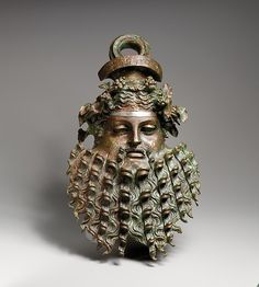 Bronze handle attachment in the form of a mask. Period: Late Hellenistic or Early Imperial Date: 1st century B.C.–1st century A.D. Culture: Greek or Roman Medium: Bronze, copper, silver The meander ornament and fillet have silver inlays, and the lips preserve some traces of copper inlay.