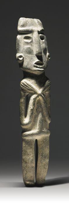 Large Chontal Stone Figure, Guerrero region - Late Preclassic, ca. 300-100 B.C. -   the hieratic figure in a reverent posture with the long slender arms crossed over the chest and hands outspread on the shoulders, legs slightly bent, the elongated head with prominent brows and nose, sunken eyes and open mouth, the cheekbones rounded, and wearing a cache-sex secured around the waist, and adorned with disk earrings; in schistic serpentine. Height: 24 in (61 cm)