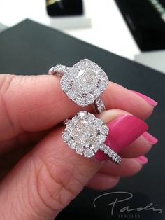"Diamond halo engagement rings with cushion cut diamond centers. One is elongated and one is a ""square"" cushion cut."