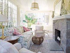 Kimberly Gieske - Shabby chic sunroom features a glossy white beadboard ceiling accented white drum pendant with nickel trim illuminating a chintz sofa adorned with pink floral pillows flanked by octagonal end tables topped with polished brass table lamps facing a rustic stone fireplace topped with mirror and white and yellow vases across from a round woven stool table flanked by pink stripe accent chairs paired with white and pink stripe pillows atop a black and white animal print rug.