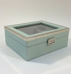 This light green faux crocodile leather jewelry box has four sections to store watches as well as two large sections for miscellaneous items. It has a glass cover and metal sides and clasp. It measure