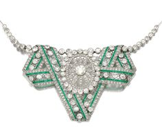 EMERALD AND DIAMOND NECKLACE/ BROOCH, CIRCA 1905.  The central jewel of folded lace ribbon design, set with calibré-cut emeralds, millegrain set with circular-cut and rose diamonds, suspended from knife edge linking, highlighted at intervals by diamonds, length approximately 450mm, accompanied by original screw driver and alternative brooch fitting, fitted case, Koch.