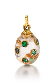 A Fabergé jewelled hardstone Egg Pendant, workmaster Feodor Afanassiev, St Petersburg, circa 1910. Carved of rock crystal and inset with circular-cut emeralds, gold loop.