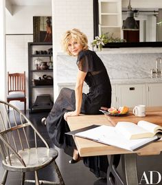 Go Inside Meg Ryan's New York City Loft Photos | Architectural Digest -- In the kitchen, Ryan wears a vintage Alaïa dress with Jill Stuart shoes. Silver Windsor chair from Wyeth.