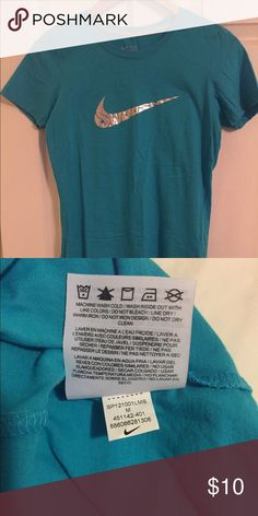 Nike t-shirt, Slim fit, M Teal color w/silver swoosh that says swoosh. Never worn. Slim fit (which is why I never wore it). Cut the tags & it ended up in storage—forgotten. The last pic is much brighter b/c used flash take pic of tagless tag; however, the 1st pic looks darker than it is. The 2nd pic shows color the best. Uugghh pics don't really show the pretty color!!  🆘🆘I'm cleaning out my closet b/c I need money for vet bills 😰😰 🆘🆘 🔽🔽💲💲discount on bundles!! Also, willing to…