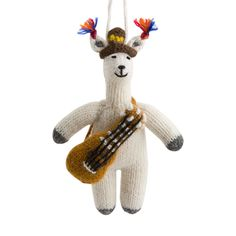 """Description Impact     This Llama with Guitar Ornament is the cutest way to invite a little Peruvian flair into your home. Made from soft alpaca wool, this hand knit ornament features a friendly llama dressed in traditional Peruvian fashion.  Alpaca wool 6""""L x 3.5""""W    Manuela Ramos // Peru Manuela Ramos provides artisan jobs to women in rural areas in addition to campaigning for women's sexual, reproductive, political, social, and economic rights. The money earned from the sale of this and…"""