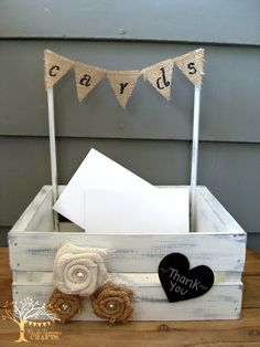 """Need a cute way to collect cards at your wedding or bridal shower? Look no further! This cute mini crate card box is a perfect addition to your gift table to collect cards and small gifts. It is painted, distressed and top sealed with all natural, no VOC products and embellished with burlap flowers, lace, tulle and a mini banner that says """"cards"""". A small chalkboard """"Thank You"""" heart shows your guests your gratitude for their gift. It measures measures roughly 10 x 12 and is 14.5 inches…"""