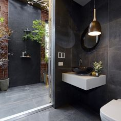 Indoor outdoor bathroom boasts black slate tiled floors and walls which frame a chunky floating sink vanity adorned with a round, black vessel sink and offset faucet below a round black vanity mirror illuminated by a modern dome pendant light.