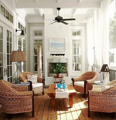 Loving this bright porch with outdoor fireplace and painting.
