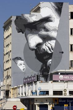 """Democritus and the Child""  [formally titled ""We Have the Power""], a street mural by the artist INO at the Piraeus near Athens."