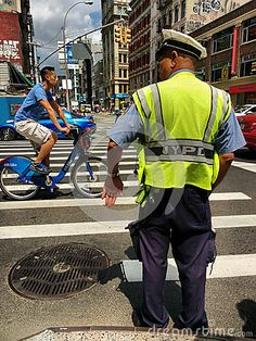 An NYPD officer wearing a high-visibility yellow reflective safety vest stands on the corner of Canal Street and Broadway, signaling to cars, pedestrians, and cyclists. A young man rides past on a Citi Bike.