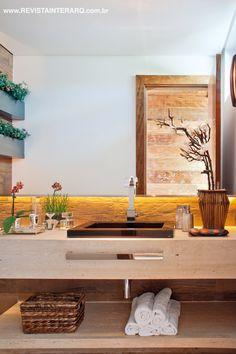 O lavabo com bancada em mármore e porcelanato amadeirado ganhou um jardim suspenso na parede