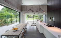 be architecten open plan raw concrete split level loft house solid surface minimal kitchen furniture origami folded white roof natural stone tiles yannick milpas Minimal Kitchen, Modern Kitchen Design, Interior Design Living Room, Küchen Design, House Design, Loft House, Kitchen Furniture, Open Plan, Building A House