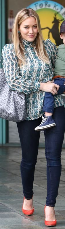 Who made  Hillary Duff's gray print handbag, green print long sleeve top, blue skinny jeans, and red pumps?