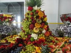 """Fresh fruits displayed in """"Mountain"""" form, additional fruits and cheeses flowing from the centerpiece. Description from adelineleighwedding.com. I searched for this on bing.com/images"""