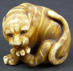 """19th C JAPANESE CARVED IVORY STUDY OF TIGER Antique hand carved Japanese ivory study of tiger. Depicted in a seated position and grooming itself. Exceptional quality. Signed with calligraphy to bottom. 19th century. Measures 1 1/4"""" height x 1 1/2"""" width"""